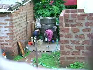 Klocka detta two het sri lankan lady getting bath i utomhus