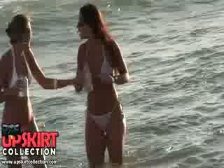 Charming bikini kuikens are staying in de water talking en having geen idee naar zijn spied