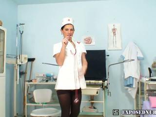 Brunette in verpleegster uniform plays met haar poesje in ziekenhuis