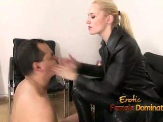 Dominatrix uz melnas āda spēlē ar a vergs
