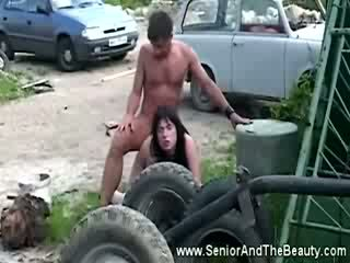 Krūtainas brunete gets fucked pret an vecs automašīna līdz antīks dude